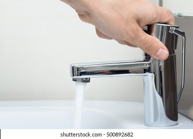 closeup of man hand and running water in bathroom