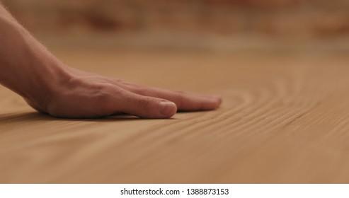 closeup man hand touches ash wood floor