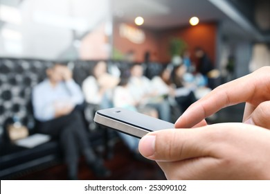 Closeup man hand using smart phone against blurred people background