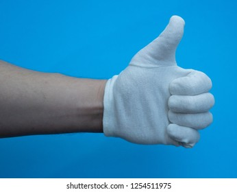 close-up man hand in white cotton glove showing thumbs up ok sign on blue background
