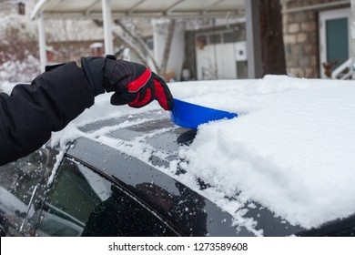 closeup of man hand in winter gloves clean snow from roof of the car with small shovel cold winter day in the city