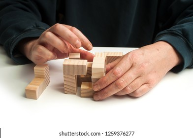 closeup of man hand with wooden puzzle  on white table background