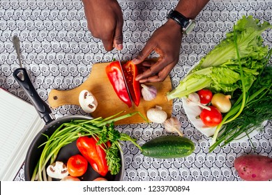 closeup of man hands african american cuts vegetables fry salad pepper, mushrooms, tomato in kitchen recipe book on the table .vegan healthy food