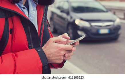 Closeup of a man hands calling a taxi with a smartphone app standing along the road