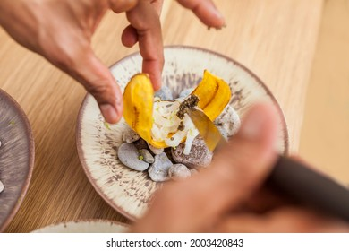 Closeup of man hands cooking banana chifles with fake squid noodles and beluga caviar
