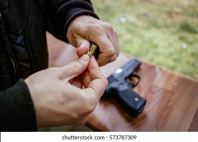 Close-up of a man hands holding and loading 9mm bullets in the pistol at the shooting range.