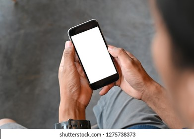 Closeup man hands holding smart phone with blank copy space screen for your text message or information content, male reading text message on cell telephone during in urban setting.