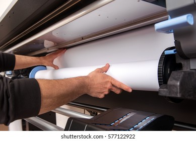 Close-up man hands loading wide format white paper roll on professional printer