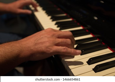 Close-up of man hands playing the piano.Warm colors in the first term and cooler in the fund