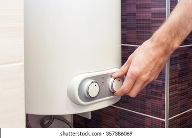 Closeup of man hands setting the temperature of water in Electric Boiler
