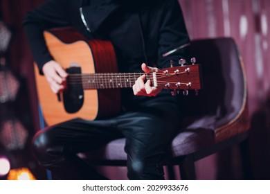 Closeup of a man hands strumming acoustic guitar.