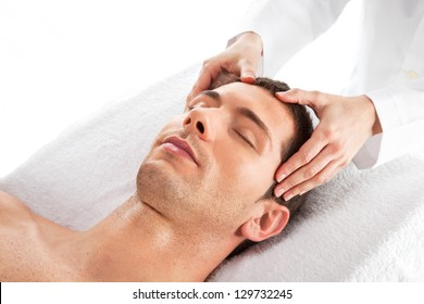 Closeup of a man having a head massage / Young man relaxed in spa