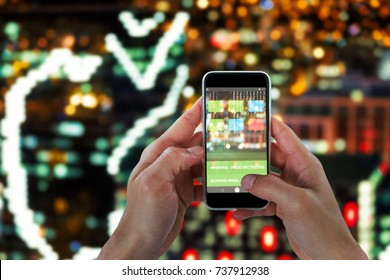 Close-up of man holding 3D smart phone against defocused image of illuminated buildings in city