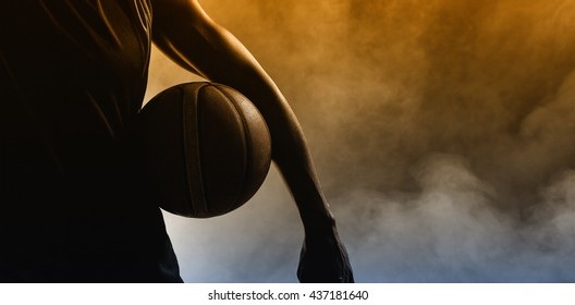 Closeup of a man holding a basketball with dark light