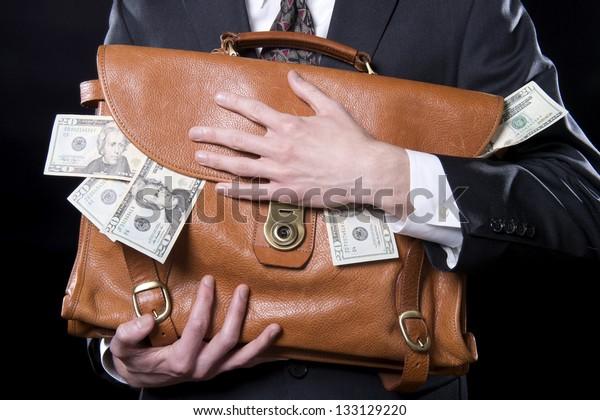 お金が胸の近くにこぼれているブリーフケースを持つ男性の接写