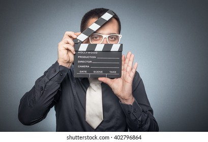 Close-up man holding movie clapper board, isolated on gray background, studio shot. Film director