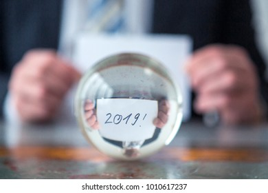closeup of man holding paper with the numbers 2019 in front of glass ball
