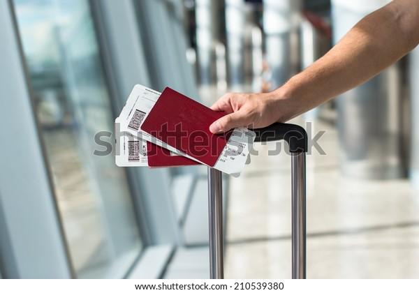 Gros plan sur un homme tenant un passeport et une carte d'embarquement à l'aéroport