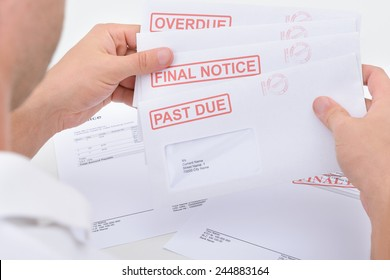 Close-up Of A Man Holding Pending Due Statements
