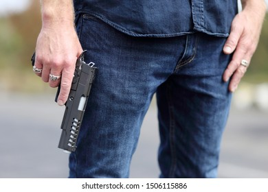 Closeup of a man holding a pistol safely with the finger off of the trigger.