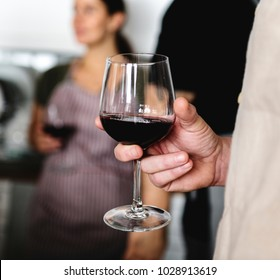 Closeup of man holding red wine glass