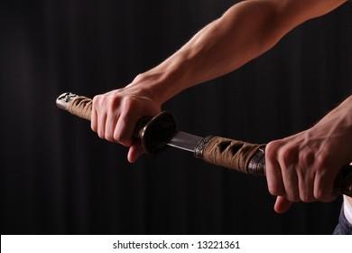 Closeup of man holding samurai sword in dramatic studio light