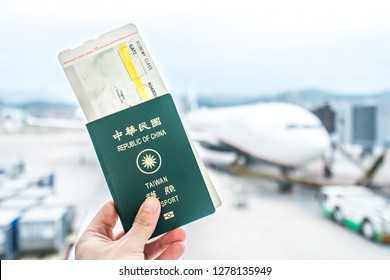 Closeup of man holding Taiwan passport and boarding pass at airport