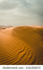 Close-up of a man jumping in dunes in a desert in Morocco at sunrise