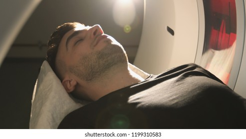 Close-up. Man lays in Magnetic Resonance Image device, making tomographic scanning. The patient opens his eyes and gets up. CT and MR scan, scanner, medical examination, Tomograph.