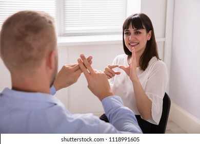 Close-up Of Man Learning Sign Language From Young Woman