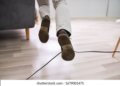 Close-up Of A Man Legs Stumbling With An Electrical Cord At Home
