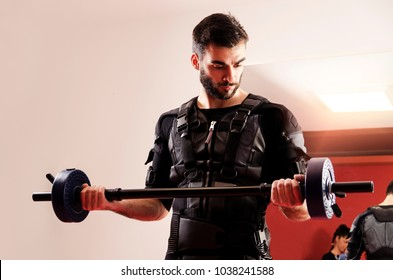 Closeup of man lifting weights in gym, using EMS stimulation