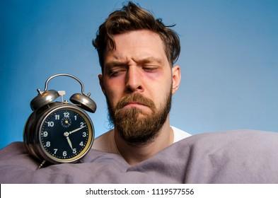 Closeup, man looking angry at the alarm clock