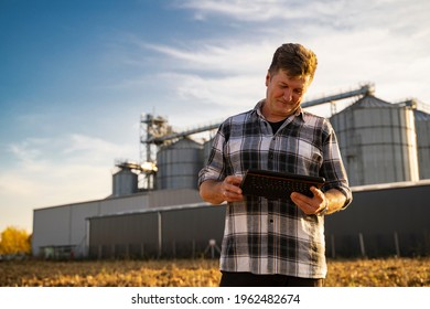 Closeup of man looking at tablet satisfied. Grain silos in background
