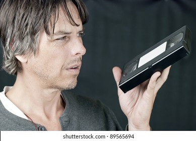 Close-up of a man looking at a video tape in confusion.