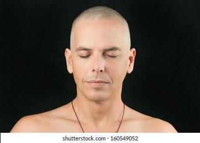 Close-up of a man meditating, shaved head and shirtless.