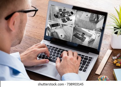 Close-up Of A Man Monitoring Black And White Video Footage On Laptop At Home