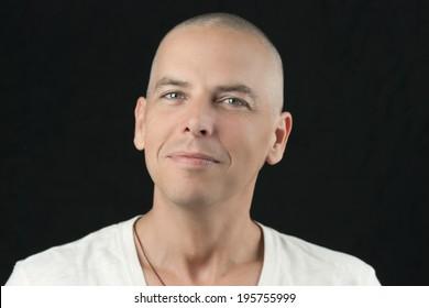 Nahaufnahme eines Mannes mit einem neu rasierten Kopf, der auf die Kamera schaut.