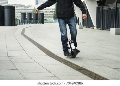 Close-up of a man on self balancing one wheel gyroscooter on light urban background. Ride on electronic gadget on the city street.