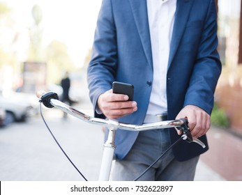 Closeup man with a phone riding a bike on the urban background. Texting businessman. Hurry concept.