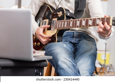 Closeup man playing a guitar and recording her music in computer