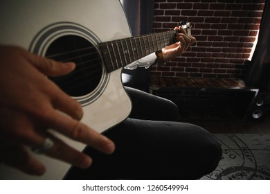 Close-up of a man playing white guitar in a loft