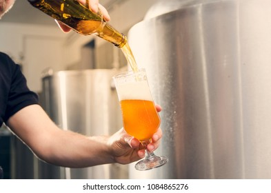 Closeup man poring beer into the unlabeled bottle in craft beer brewery