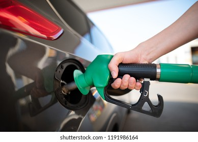 Closeup of man pumping gasoline fuel in car at gas station. Gas pump nozzle in the fuel tank of a gray car