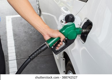 Closeup of man pumping gasoline fuel in car at gas station