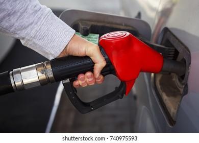 Closeup of man pumping gasoline fuel in car at gas station. fuel car at gas station. Pumping gas at gas pump.