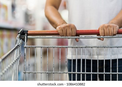 Close-up of Man pushing shopping cart in a supermarket