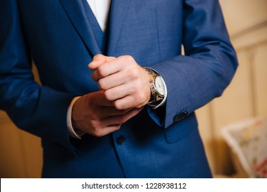 559b39db9118 Close-up man puts on a gold watch with a leather belt, businessman is