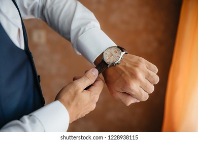 Close-up man puts on a gold watch with a leather belt, businessman is dressed in a stylish suit, a white shirt