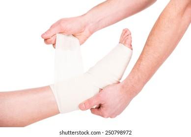 Close-up man is putting bandage on injured feet.